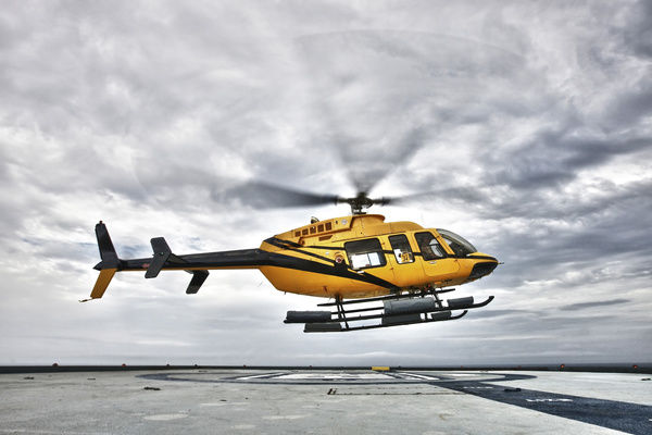 A Bell 407 utility helicopter prepares to land on the helipad of an oil rig