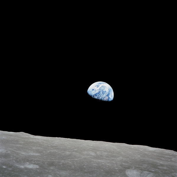 December 24, 1968 - The rising Earth is about five degrees above the lunar horizon in this telephoto view taken from the Apollo 8 spacecraft near 110 degrees east longitude. The horizon, about 570 kilometers (350 statute miles) from the spacecraft
