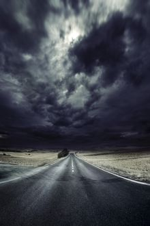 An asphalt road with stormy sky above, Tuscany, Italy