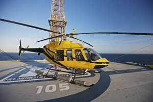 A Bell 407 utility helicopter on the helipad of an oil rig