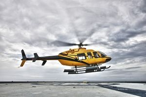 A Bell 407 utility helicopter prepares to land on an oil rig