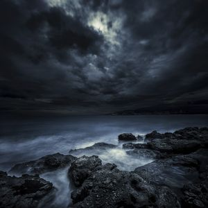 Black rocks protruding through rough seas with stormy clouds, Crete, Greece