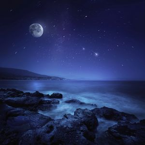 Rocks seaside against rising moon and starry field, Crete, Greece
