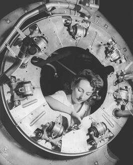 A woman assembles part of the cowling of a B-25 bomber motor. circa 1942